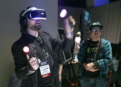 Chris Scott Barr (left) of the SlashGear site tries the PlayStation VR with Naoki Yoshimura of Famitsu. Photo: Liz Hafalia, The Chronicle