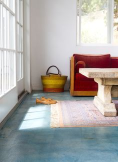 Sea blue colored concrete floor with rustic wooden coffee table & faded persian rug.
