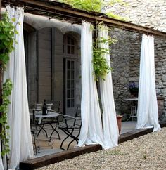 """""""Breezy white curtains give this patio a sophisticated allure"""" via homedit. backyard covered patio inspiration."""