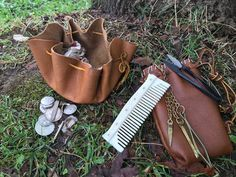 Since Viking Age clothing lacked pockets, anything needed for daily carry would need to be carried in pouches on the wearer's belt. The pouch on the left, made in the circular drawstring configuration, is used to carry monetary goods, such as silver. The second pouch, on the right, is used to carry grooming and hygiene supplies.