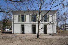Die schlichte Gartenfassade gliedern Holzfensterläden, fanzösische Fenster und Bossenputz.