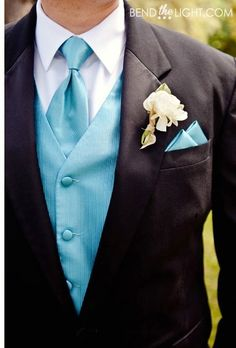 Groomsmen attire: black suit, white shirt, blue vest, blue tie, and they would have a blue boutonnière. Same shade of blue as the bridesmaids' dresses.