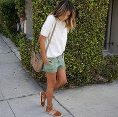 A blogueira Julie Sarinana com look verão, shorts verde, t-shirt e espadrille marrom.