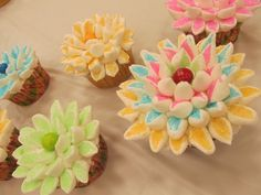 Cupcakes decorated with marshmallows- sliced & dipped in colored sugar. Center is a skittle. How adorable.
