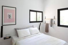 בחדר השינה מתלה עץ ומדפי צד מברזל שחור מכופף, שתיכננו זוג מעצבי הפנים של הדירה (צילום: אביעד בר נס)