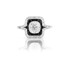 Art Deco Platinum, Diamond and Black Onyx Ring   Centering one cushion-shaped diamond approximately 1.15 cts., framed by calibre-cut black onyx and 34 old-mine and single-cut diamonds, circa 1920.