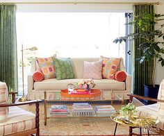 Use a glass coffee table and leggy furniture to open up any living room, and give it a larger look. Combine colorful fabrics to bring it all to life./