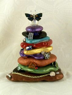 This idea started with a natural rock cairn tower I made in my garden. This hand-painted sculpture came together very slowly. I worked on it, on