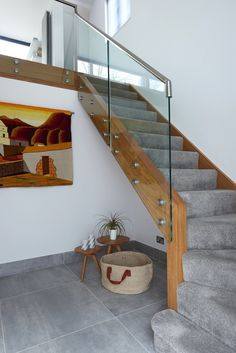 Infinity Integral glass and wood renovation with metal railings and grey carpet. New staircase design for a beautiful home. Wall decorated with African inspired printed artwork. Photographed by Matt Cant and styled by Nicola Wilkes from My Settled Home. Tiled Staircase, Carpet Staircase, House Staircase, Staircase Railings, Hall Carpet, Stairs With Carpet, Grey Stair Carpet, Grey Carpet Hallway, Bannister
