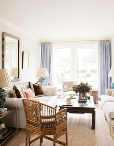 """Natural linen on the tufted sofa and ticking stripe on the settee keep the living room of this New York apartment from being """"too stuffy or precious,"""" says designer Ashley Whittaker. """"And I love the rustic bamboo chair in place of a larger armchair. It takes up less space visually, and it adds vintage charm."""""""