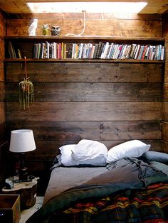 cozy nook... wood walls, built-in bookshelf, owl decor, tree trunk stand, plaid bedding and skylight... charming.