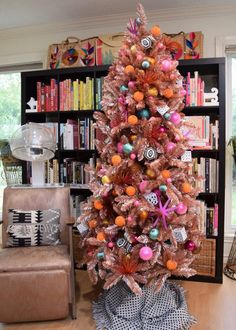 Christmas tree in rose gold in front of a book shelf