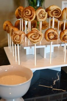 mini cinnamon rolls on a stick with frosting dipping sauce