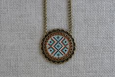 The geometric pattern in this hand-embroidered necklace is cross-stitched on an off-white color Murano fabric with threads in emerald green, mint, firebrick orange and brown colors. The embroidery fabric is 32 stitchs per inch and the threads are DMC, high quality on embroidery