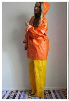 Lady wearing orange rain jacket with yellow rain pants Raincoat Jacket, Pvc Raincoat, Rain Pants, Rain Jacket, Vinyl Clothing, Rubber Raincoats, Heavy Rubber, Rain Gear, Windbreaker