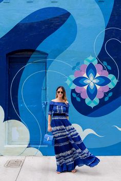 Jennifer Lake Style Charade wearing a blue pleated Self Portrait maxi dress, and blue Henri Bendel bag at a blue swirl mural wall