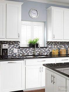 A pop of purple adds subtle color to this gray glass tile backsplash.