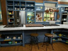 Welcome to The Kitchen : As the centerpiece of the set, this expansive kitchen features two cooktops, an oversize refrigerator, a deep sink and a stretched island with raised barstools for seating. Just recently it was updated with fresh coats of Dolphin Blue Behr Interior paint.