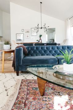 Living room wth layered rugs and a velvet sofa