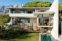 Au coeur de la nature, une maison de baies vitrées et de nature luxuriante