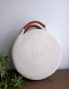Round white bag made out of cotton rope and up-cycled soft brown leather. This bag is durable and roomy enough to fit all your necessities - measures about 12 inches across and 2 inches deep, with about 3 inch handles. Find a simple cotton rope basket bag Round Basket, Round Bag, Rope Crafts, Diy And Crafts, Leather Handle, Leather Bag, Brown Leather, Basket Bag, Crochet Handbags