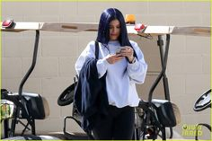 Kylie Jenner Debuts Midnight Blue Hair After Saying Her Hair Is Partially 'Destroyed': Photo #941092. Kylie Jenner looks up from her phone while leaving a photo shoot in Los Angeles on Saturday afternoon (March 12).    The 18-year-old reality star hung out with a…
