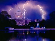 The White House turns purple during a storm and lightening flashes across the sky