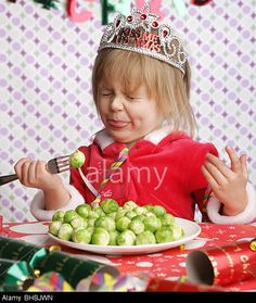 868029c99e84a A three year old sitting at a table with Christmas decorations and a plate  full of