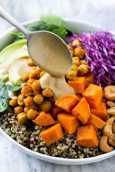 These vegan buddha bowls are loaded with colorful veggies, sweet potatoes, roasted chickpeas and cashews, all topped off with a creamy tahini dressing.