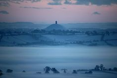 Mist forms across fields as the sun sets over the snow-covered Somerset levels near Glastonbury Tor