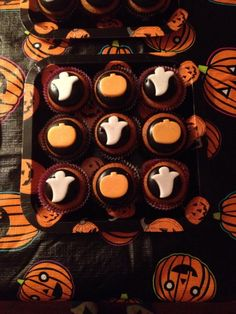 Our Halloween/Housewarming Party: Pumpkin cupcakes with chocolate marshmallow frosting topped with adorable fondant ghosts and pumpkins. I used the center shapes from my Wilton Halloween Linzer Cutter set, and I brushed my ghosts with white pearl dust and my pumpkins with gold pearl dust. They looked awesome against the black!