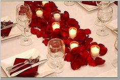 Rose petal table scape with candles, white tablecloth and plates and red  cloth napkins that match the petals as closely as possible (or contrast would be good too.)