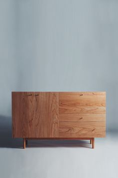 """Inspired by the Scandinavian aesthetic of bold simplicity, the Rex Sideboard is a celebration of wood character and clean, balanced line. The left side features two doors opening to adjustable shelves. On the lower right side you'll find a large and a small drawer. Open the drop-down door on the upper right and you'll find a mirrored compartment perfect for wine and spirit or glassware storage. * Dimensions: 60"""" x 19"""" x 36 1/2"""" * Materials: Cherry wood, brass, mirror * Soft-close Blum hinges and slides throughout * Handcrafted in Brooklyn"""