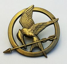 The Mockingjay pin worn by Katniss Everdeen during the and annual Hunger Games. Hunger Games Party, Hunger Games Movies, Hunger Games Trilogy, Game Party, Divergent Trilogy, Hunger Games Mockingjay Pin, Hunger Games Catching Fire, Tribute Von Panem, This Is A Book