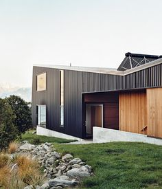 "The home is mostly clad in black trapezoidal-profile steel, with cedar boards lining what the owners call the ""human spaces""—external pas..."