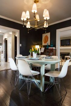 Loving the almost black dining room walls with white trim and modern chairs. (Nest Studio Blog)
