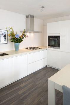 Zeer strakke moderne keuken. Mooi contrast tussen het donkere laminaat en de witte keukenmeubels.
