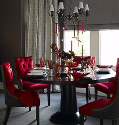 City Chic  Luxurious fabrics for chairs and curtains give this dining room a real sense of grandeur, while glossy furniture and colored glassware create a sophisticated mood against a rich backdrop of chocolate and cranberry.