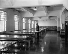 A prison guard looks over the spotless mess hall at the Federal Prison on Alcatraz Island in 1956