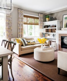Warm grey walls, a dark sisal rug and soft cream upholstery form a quiet backdrop for grey and yellow damask drapes and hits of yellow in accessories like the custom toss cushions.
