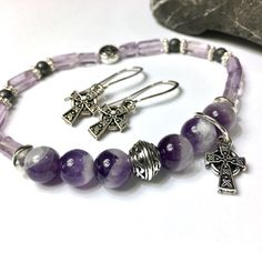 A shop favorite!  Amethyst & hematite bracelet  •Choice of cross or shamrock charm •Coordinating earrings are optional •Gift-ready packaging & gift card  Perfect for -  •Mother's Day •First Communion •Confirmation •Graduation •Birthday •Bridesmaids