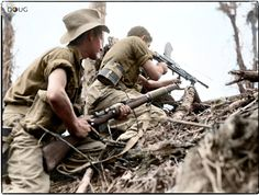 Pte. Inglis and Pte. J.Pie of 'C' Company 2/8th Australian Infantry Battalion, 6th Australian Division give covering fire against Japanese positions, to assist an outflanking movement on Mount Shiburangu near Wewak, New Guinea 27th June 1945.