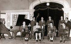 """Orquesta Típica de Oldimar Cáceres. Fonoplatea de Radio Carve, en programa """"Bajo las luces de Kolynos"""". Palacio Díaz. Año 1958 (aprox.). (Foto: Archivo personal Héctor Baron. Autor: S.d) De izquierda para derecha Roberto Dionigi (piano), José Budano (bandoneón), Néstor Casco (contrabajo), Oldimar """"Pocho"""" Cáceres (bandoneón), Luis Altieri (viola), Héctor Barón (bandoneón), Esteban Craciun (violín), Carlos Martín (violín), Rómulo Bosch (bandoneón) y Carlos Magallanes (presentador de la…"""