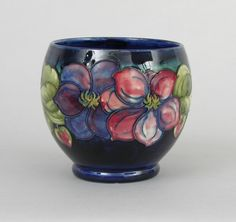 """A Moorcroft Glazed Ceramic Bowl, ca. 1947-1953  A beautiful deep bowl of bulbous form on a small foot. Hand painted and tube-lined with polychrome floral motif on a cobalt background. Painted in blue signature """"WM"""" and impressed factory mark """"Moorcroft Made in England"""" under glaze on the bottom. Measures . 5-1/4""""H x 5-3/4D."""