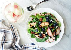 A glass of peach sangria next to a fork ready to dig into a bowl of fresh, bright peach blueberry spinach salad; the grill marks on the peaches are particularly prominent.