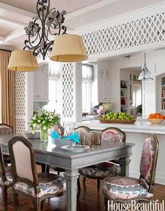 Just a Touch of Color:     To balance the diamond pattern on the walls, Allison Caccoma used softer lines and curves in this breakfast room's chandelier and chairs. The floral colors of the fabric, a Robert Kime suzani, provides a burst of color against the all-white kitchen and helps the space feel like an extension of the garden.