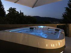 Vue de nuit d'un spa Jacuzzi® J-500™posé sur la terrasse de l'hôtel Relais san lorenzo en Italie.
