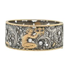 Mid-Victorian Silver Diamond Gold Figural Filigree Bracelet. A rare and very unusual mixed metals bracelet from the Mid-Victorian (ca1870) era! Made of sterling silver and 15kt rosy yellow gold (indicating English origin), this beautiful piece is particularly wide and features a fine mixed metals design that graces the surface on both sides. The elaborate filigree design includes an array of richly detailed floral swirls surrounding the figure of a woman in the center. c 1870