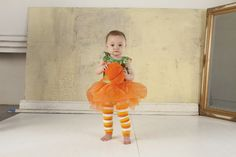 Little girl wearing BabyLegs Candy Corn legwarmers and tutu pumpkin costume. These warmers will be available Fall 2012 - Halloween!