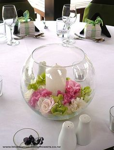 Wedding table centerpiece with fishbowl vase filled with pale pink and white lisianthus, roses and green and white hydrangea, with a pillar candle at the centre Visit us here: www.blossomweddingflowers.co.nz Friend us here: www.facebook.com/pages/Auckland/Blossom-Wedding-Flowers/2...